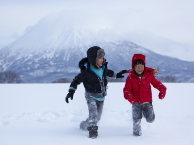 Two Kids Walking On Snow With Mt Yotei In The Background